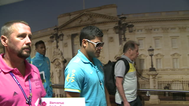 Long walking shot of Hulk as Brazil's soccer squad arrives at Heathrow for 2012 London Olympics / Heathrow greeter walks alongside him