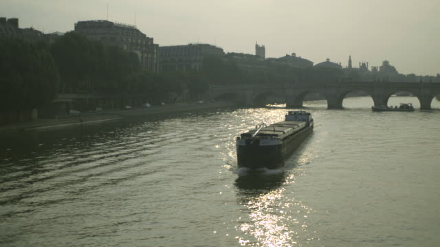 A long, wide barge powers down the River Seine towards the Pont des Arts bridge (showing the Tuileries area and the Pont Neuf) in Paris, France.