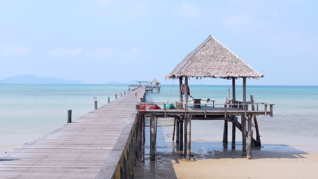 long wooden jetty with small hut and crystal-clear ocean and blue sky - long stock videos & royalty-free footage