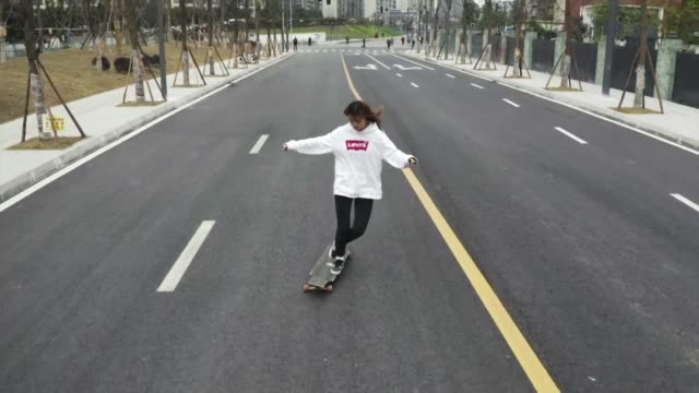 vídeos de stock e filmes b-roll de longboarder mu qing skates through the mega city of chengdu in southwest china deftly dancing on and off her ride as a friend tails her from behind... - southwest usa