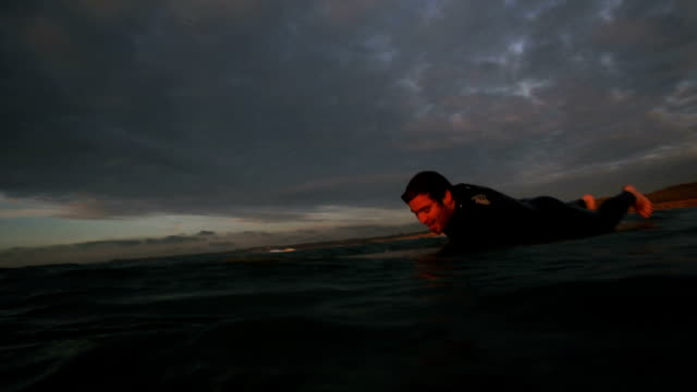 longboarder paddles into sun set - channel islands england stock videos & royalty-free footage