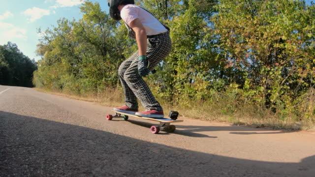 stockvideo's en b-roll-footage met longboarder met een draagbare camera die op de berg rijdt - moed