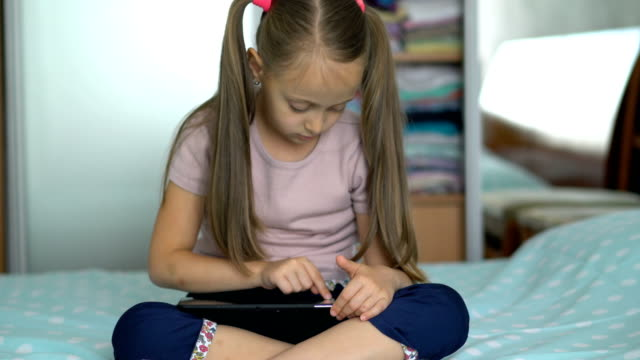 Long-haired girl playing with the digital tablet at home