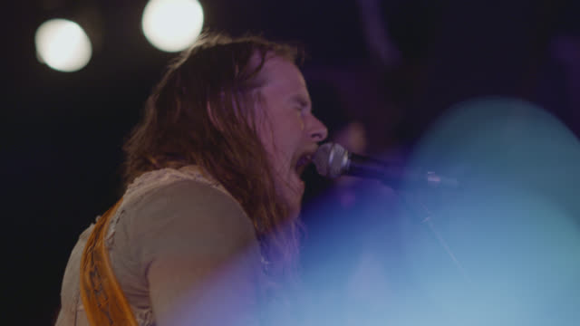long-haired rocker sings and plays guitar on stage in crowded club - solo performance stock videos and b-roll footage