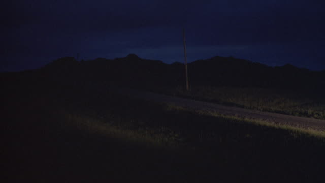 Long-shot of a car driving along a country road at night.