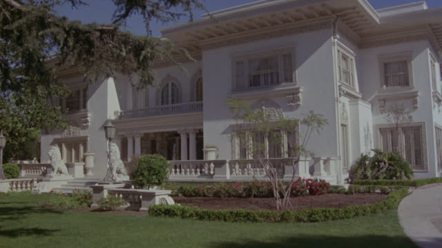 Long-shot of a white mansion in Los Angeles.