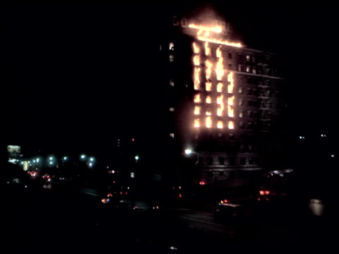 Long-shot of an apartment building burning and emergency vehicles arriving.