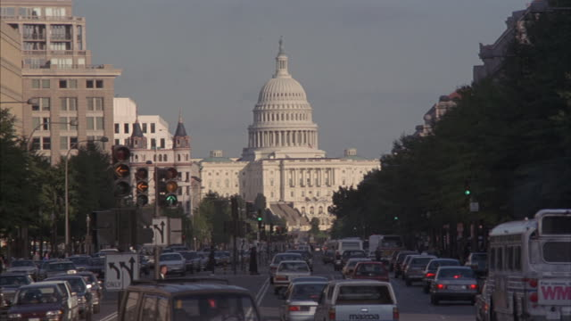 Long-shot of pedestrian and vehicular traffic in front of the US Capitol.