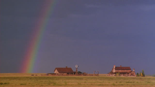 Long-shot of ranch with a stormy dark sky and a rainbow.