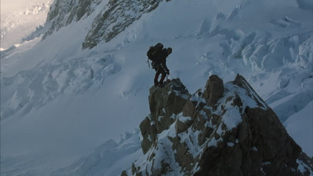 Long-shot of two climbers ascending a rock spire in the middle of a snow-covered mountain range.