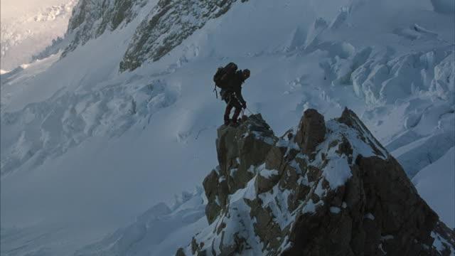 vídeos y material grabado en eventos de stock de long-shot of two climbers ascending a rock spire in the middle of a snow-covered mountain range. - alta utah