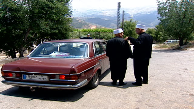 long-shot of two druze sheikhs talking before one of them gets into a car. their attire indicates they are uqqals, who have access to the literature... - literature stock videos & royalty-free footage