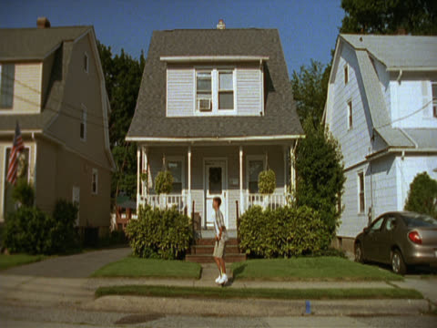 a longshot showing houses in a leafy, suburban street. a boy on a pogostick bounces along the sidewalk, travelling from right to left. long island, new york, usa - bouncing stock videos & royalty-free footage