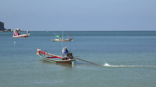 a longtail boat goes out to sea - longtail boat stock videos & royalty-free footage