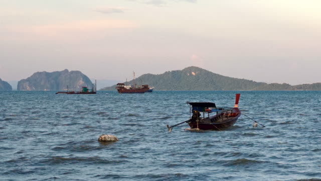 longtail boat, ko lanta, thailand, with ko talabeng and ko bubu in the distance - longtail boat stock videos & royalty-free footage