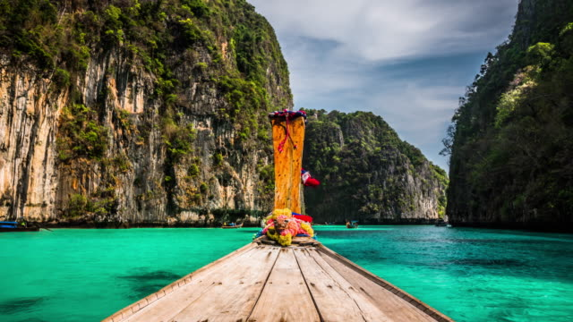 vídeos de stock e filmes b-roll de pov: longtail boat sailing through tropical lagoon in thailand - navio de passageiros