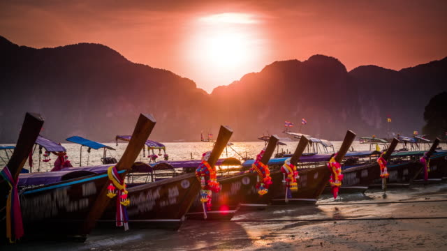 vídeos de stock e filmes b-roll de longtail boats in thailand at sunset - ilhas phi phi