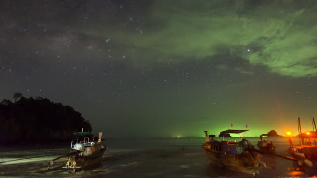 longtail boats mooring at beach during night time with stars and milkyway constellation over head - low tide stock videos & royalty-free footage