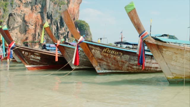 longtail boats on tropical beach - phi phi islands stock videos & royalty-free footage