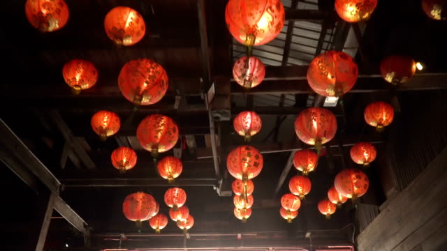 look at red asian lanterns under wooden buliding - pechino video stock e b–roll