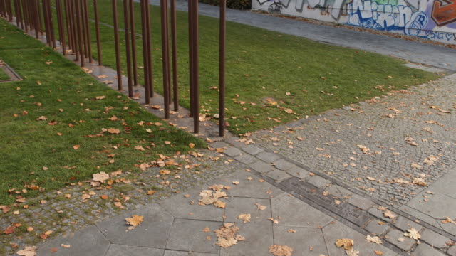 A look to the actual Berlin wall and its memorial built of iron robs at this place where the wall stood at the Bernauer str in a sunny autumn day...