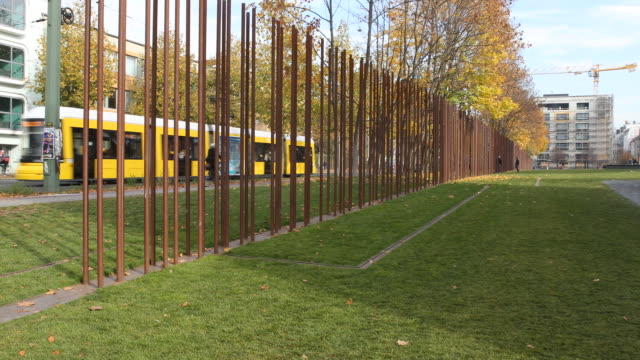 A look to the actual Berlin wall memorial at the Bernauer str in a sunny autumn day The Berliner yellow tram passes behind the Wall memorial
