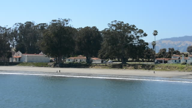 looking at a long stretch of beach in san simeon bay central coast of california people walking on the beach by the water - water surface stock videos & royalty-free footage