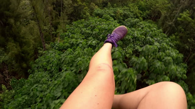 pov looking at girl's legs as she ziplines over canopy of trees - turtle bay hawaii stock videos and b-roll footage