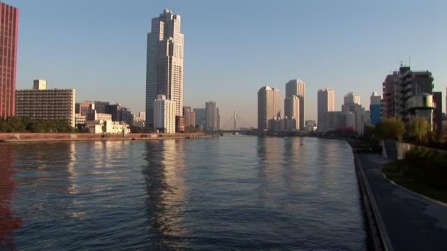 looking at skyscrapers across sumida river with view of chuo-ohashi bridge in distance / tokyo - 2005年点の映像素材/bロール