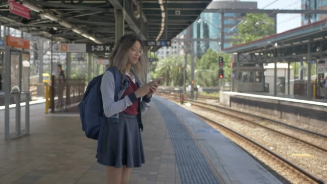 looking at train timetable on smart phone - schoolgirl stock videos and b-roll footage
