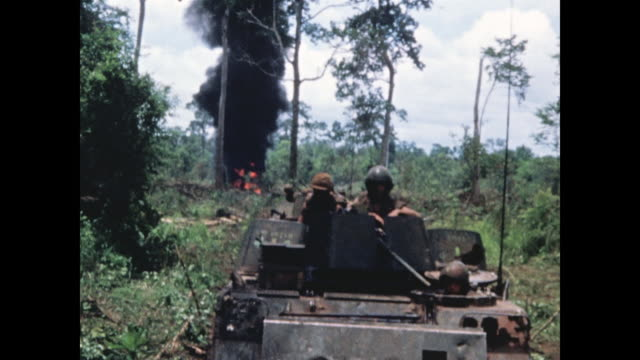 looking back at armored personnel carriers as they rumble through the jungle with plume of black smoke and flame behind. camera tilts up to follow... - vietnam war stock videos & royalty-free footage