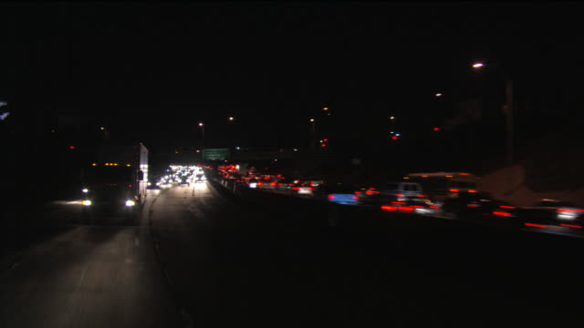 looking back at traffic in both directions on an la freeway at night - artbeats stock videos & royalty-free footage