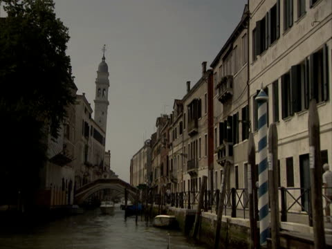 pov looking back on a canal boat navigating through narrow canal under bridges, venice, italy (sound available) - spira tornspira bildbanksvideor och videomaterial från bakom kulisserna