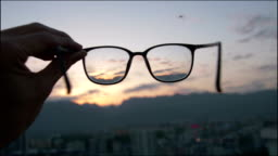 Looking city sunset through eyeglass