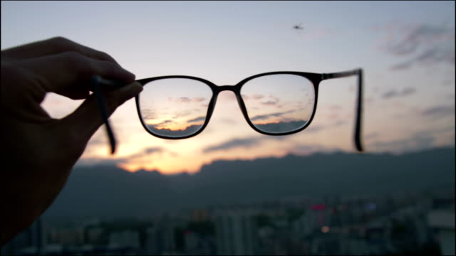 vídeos de stock e filmes b-roll de looking city sunset through eyeglass - visão