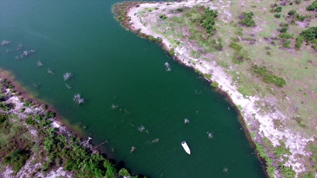 aerial: looking down above a boat floasts along georgetown lake in central texas - georgetown texas stock videos & royalty-free footage