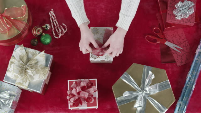 looking down at gifts on table as person places them on table - ribbon bow stock videos & royalty-free footage