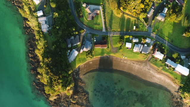 looking down at houses next to beach. - baia delle isole nuova zelanda video stock e b–roll