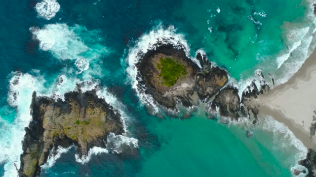 looking down at surf beach waves splashing on rocks. - new zealand culture stock videos and b-roll footage