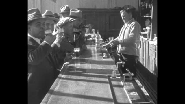 looking down bar with customers drinking and bartender serving; many of the men wear suits and hats - bartender stock videos & royalty-free footage