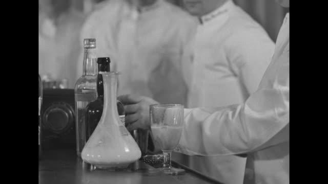 vidéos et rushes de looking down bar with men of graduating class of bartenders school along bar, instructor stands behind bar beside table full of bottles of liquor /... - shaker