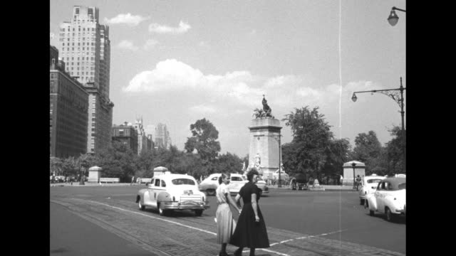 Looking down Central Park South from Columbus Circle streetcar tracks in road pan park to include USS Maine National Monument carriages by curb /...
