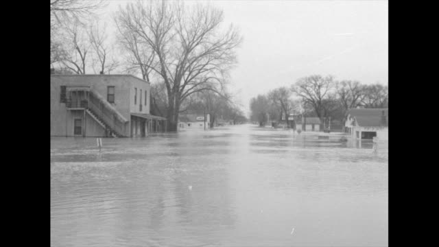 Looking down flooded street buildings and trees to side