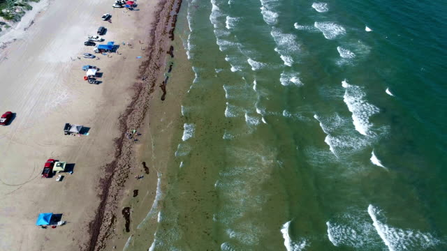 Looking down from above flying over Water along Padre Island Beach a long barrier Island along South Texas with People and Summertime Fun
