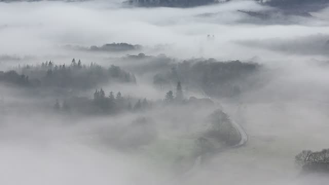 looking down into the langdale valley above valley mist formed by a temperature inversion on loughrigg, near ambleside in the lake district national park, with cars driving on the hawkshead road. - fog stock videos & royalty-free footage
