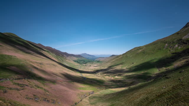 looking down newlands valley in the cumbrian lake district on a sunny day with clear blue skies in the distance rapidly moving clouds cast shadows on the floor of the u-shaped glacial valley - valley stock videos & royalty-free footage