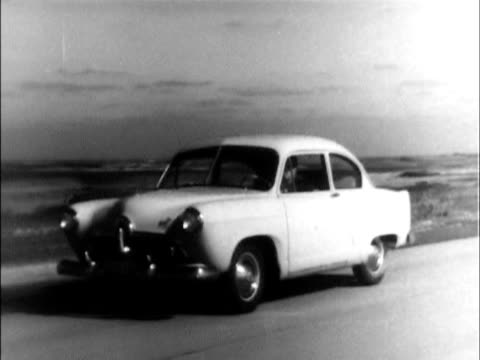 ws ha looking down on 1951 kaiser in dealer showroom / dissolve to ws 1951 henry j driving on highway / wipe to ws kaiser and henry j driving side by... - 隣り合わせ点の映像素材/bロール