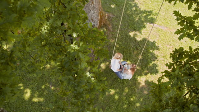 CS Looking down on a couple swinging amongst the trees