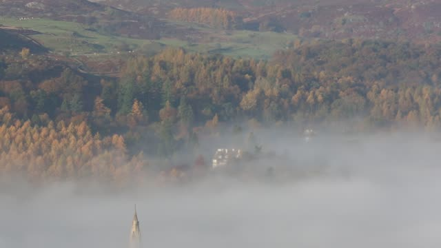 looking down on ambleside with valley mist in the autumn time, lake district, uk, with st mary's church spire poking through the mist. - spire stock videos & royalty-free footage