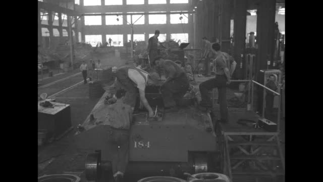 vs looking down on factory floor where sherman tanks being assembled workers on floor / looking down row of tanks on assembly line mechanic working... - 武器点の映像素材/bロール